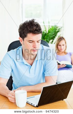 Concentrated Man Working On His Laptop With His Girlfriend Reading In The Background