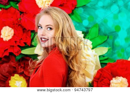 Beautiful joyful young woman with magnificent blonde hair posing on a background of bright large flowers. Beauty, fashion. The spirit of summer.