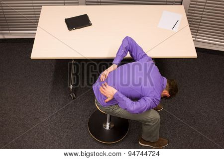 man with lower back pain in office work exercising