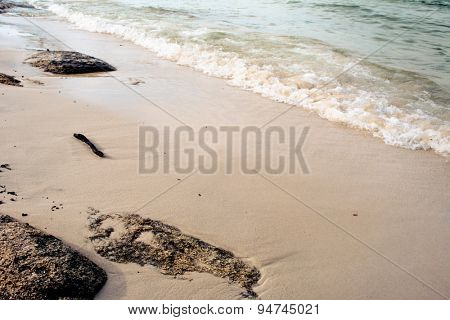 Sandy beach with stones and waves