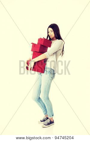 Pretty teen holding a lot of presents