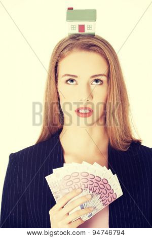 Beautiful woman holding a house model on head