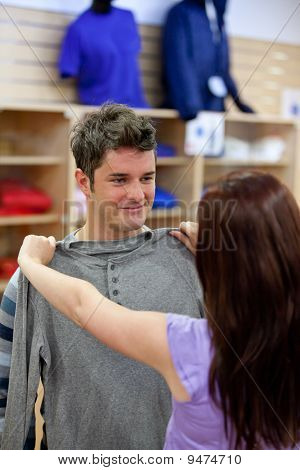 Handsome Man With His Girlfriend Trying On Clothes In A Shopping Centre