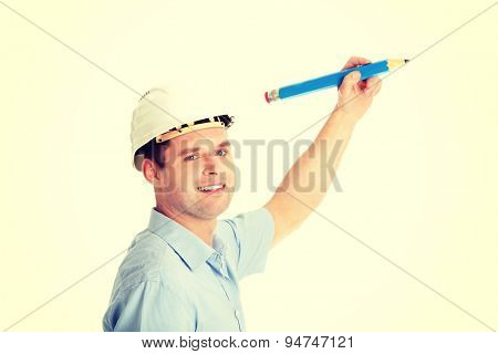 Engineer in white helmet writing on copy space with huge pencil