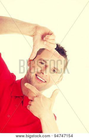 Closeup of confident happy man framing his face