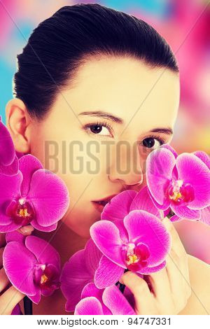 Young beautiful woman with an orchid flower
