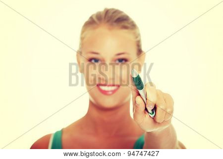 Young blonde woman holding a pen