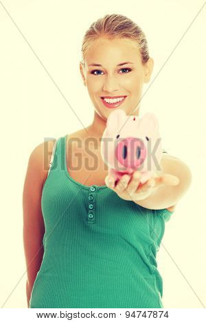 Young blonde woman holding piggybank
