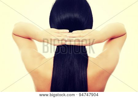 Young brunette woman touching her hair