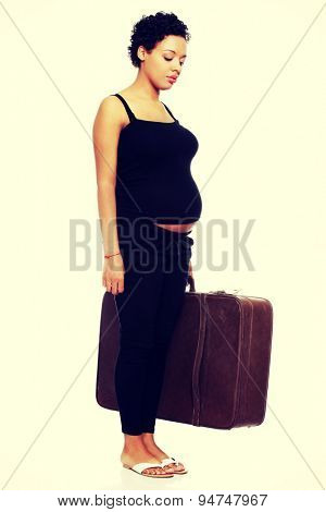Sad pregnant woman with a lugagge