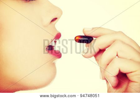 Young beautiful woman taking pill