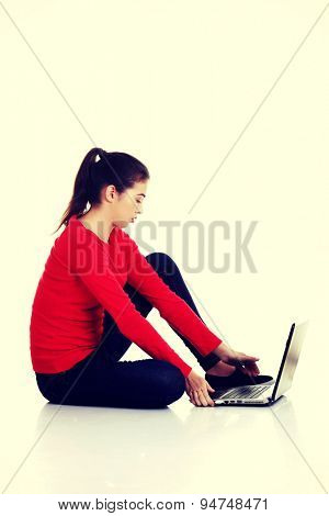 Beautiful young woman sitting with a laptop