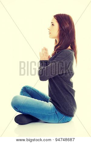 Pretty student girl meditating in lotus pose. She is relaxed and concentrated