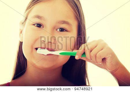 Little smiling girl brushng teeth