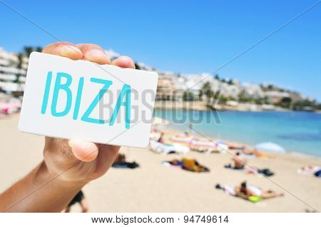 closeup of the hand of a young caucasian man showing a signboard with the word Ibiza, written in it, in Ses Figueretes Beach in Ibiza Town, Spain