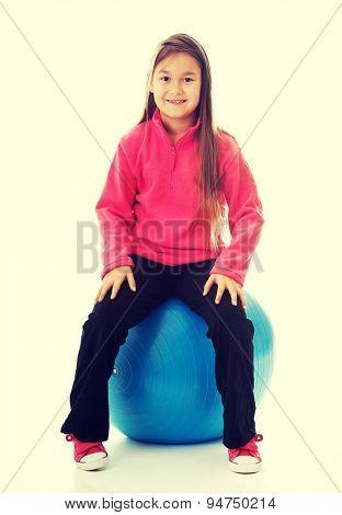 Little girl sitting on a big ball