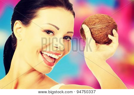 Young nude woman holding a coconut
