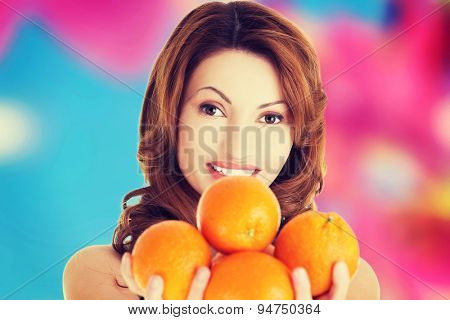 Happy beautiful woman holding oranges