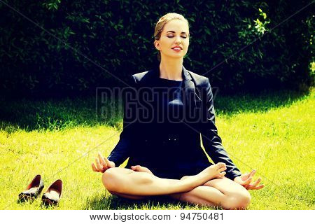 Beautiful businesswoman relaxing by yoga