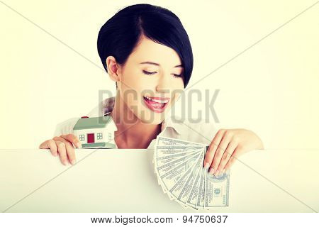 Beautiful woman holding a house model and money clip