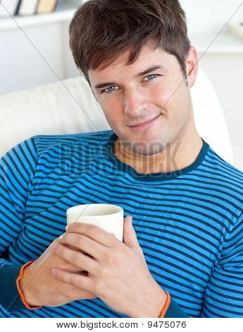 Happy Man Resting On His Couch With A Cup Of Coffee
