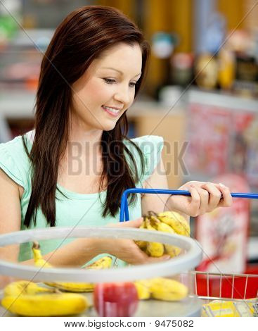 Portrait Of An Attractive Woman Buying Bananas And Apples