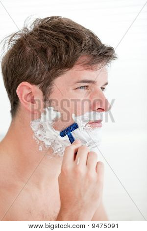 Portrait Of A Serious Man Shaving Looking Away Standing In The Bathroom
