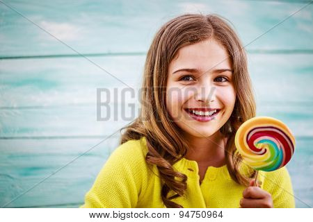 Cheerful young girl with a lollipop