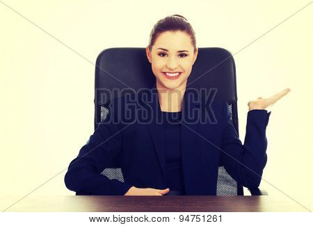 Blonde businesswoman inviting to an office