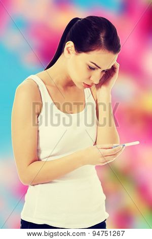 Worried woman with positive pregnancy test