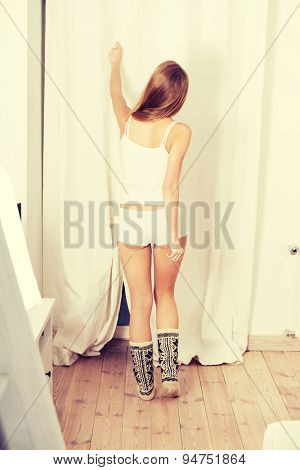 Young blonde woman covering window