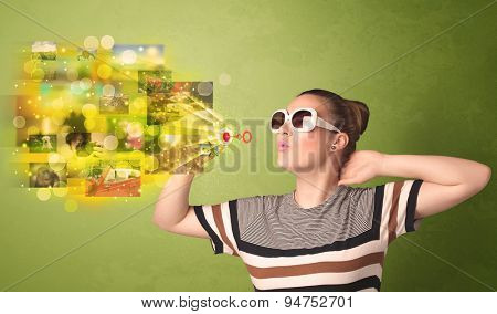 Cute girl blowing colourful glowing memory picture concept on green background