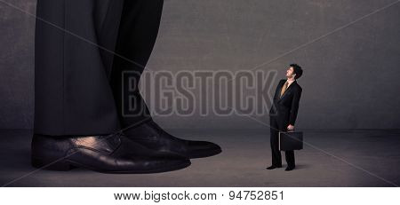 Huge legs with small businessman standing in front concept on background