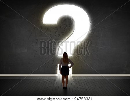 Business woman looking at wall with a bright question mark concept