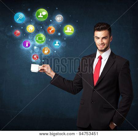 Businessman standing and holding a white cup with colorful setting icons coming out of the cup