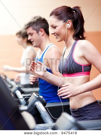 Beautiful Female Athlete Standing On A Running Machine Listening To The Music