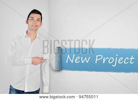 Young man painting New project word on wall