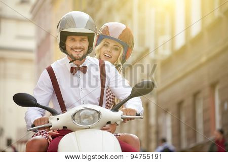 Cute couple riding a scooter on a sunny day in the city