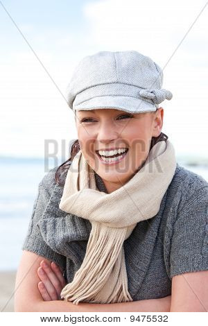 Cheerful caucasian woman with cap and scarf standing on the beach