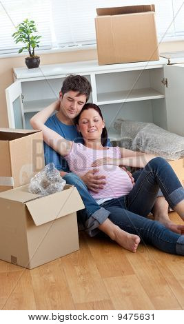 Future Parents Relaxing On The Floor During A Break After Unpacking Boxes