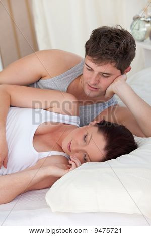 Affectionate Young Man Looking At His Pregnant Wife Sleeping Both Lying On The Bed