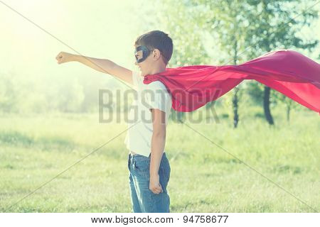 Super Hero Kid having fun outdoor. Superhero little boyover nature green blurred background