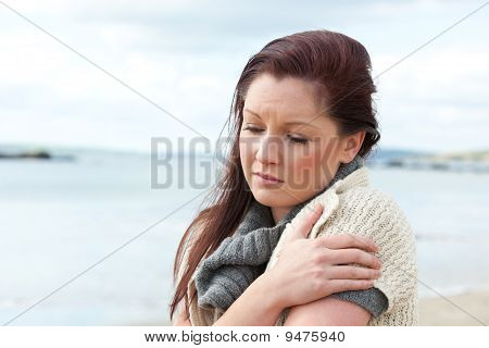 Cold young woman standing on the beach