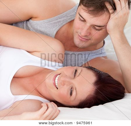 Close-up Of An Affectionate Man Looking At His Pregnant Wife Lying On The Bed