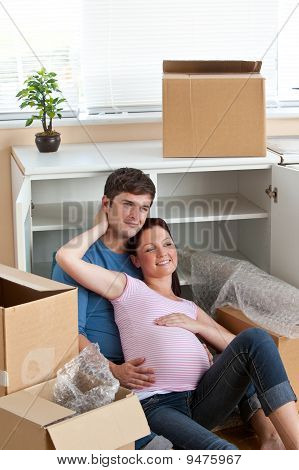 Adorable Couple Sitting On The Floor In Their New House During Removal