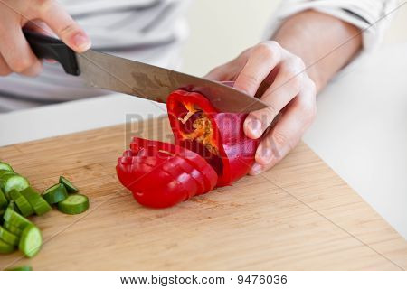 Close-up Of A Man Cutting Red Pepper Standing In The Kitchen