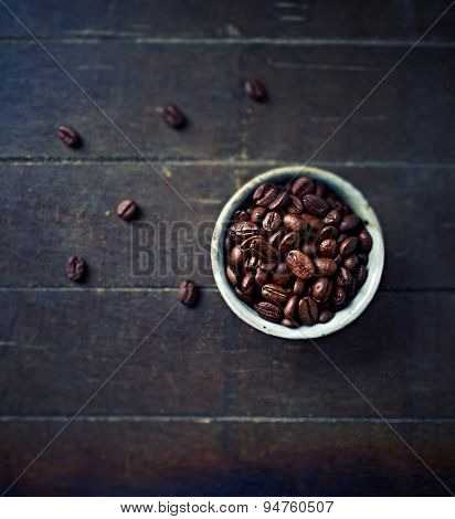 Dark roasted coffee beans in a ceramic cup