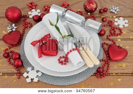 Christmas holiday dinner place setting with plates, antique cutlery, napkin, bauble decorations and mistletoe over oak background.