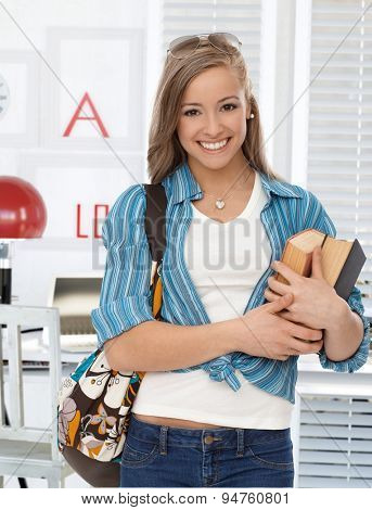 Happy young college student holding books, smiling, looking at camera.