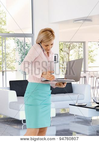 Busy casual caucasian blonde businesswoman working at home using mobile phone, folder in hand, standing, talking, elegant.